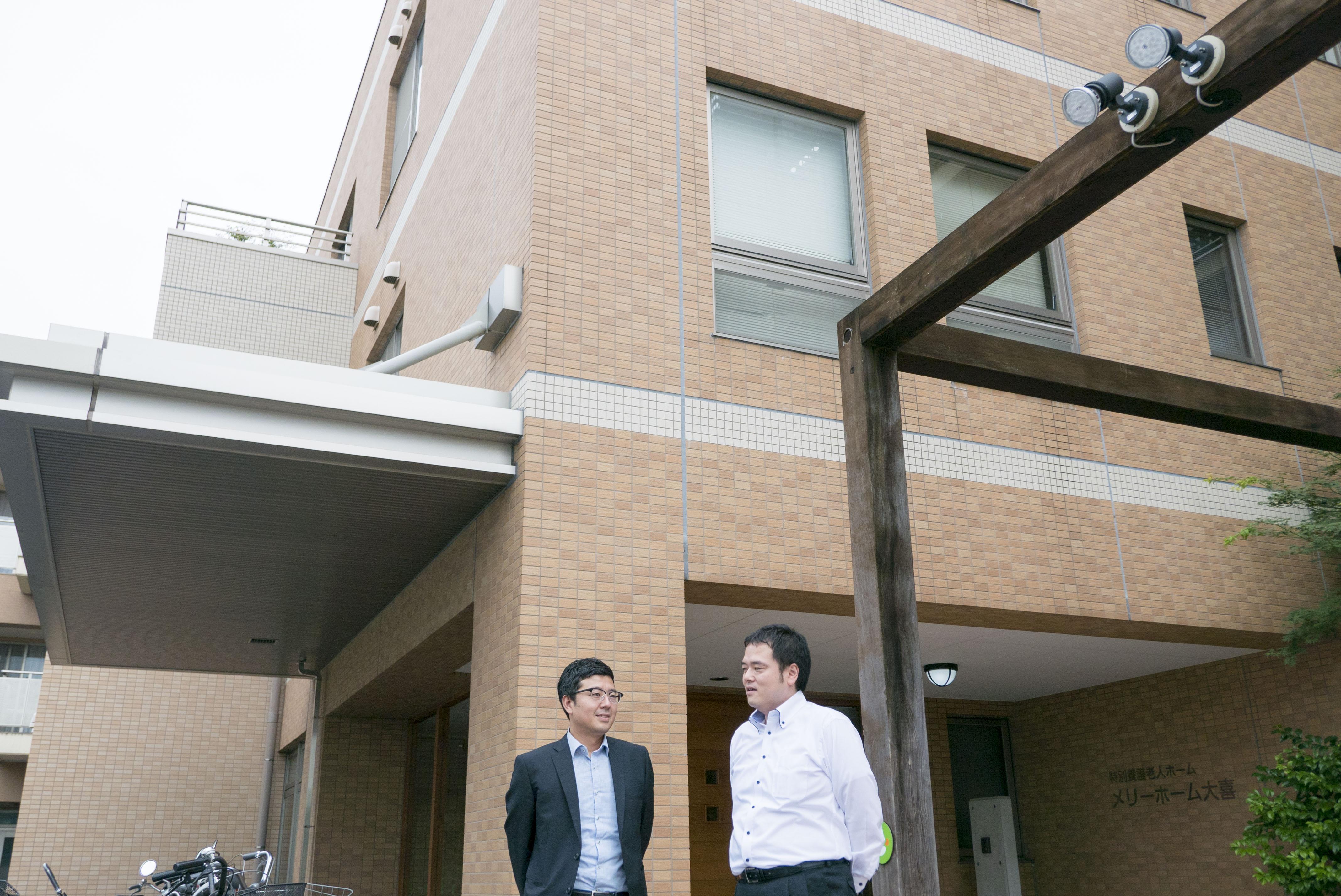 介護施設の前で今後の展開を話し合う斉藤先生と本部の荻原さん